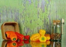 Pimientas, ajo, con pimienta negra, y aceite de oliva con de la cocina todavía de los utensilios vida Imagen de archivo