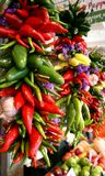 Pimientas, ajo, y flores que cuelgan en mercado Imagenes de archivo