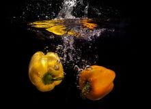 Pimientas amarillas en agua Imágenes de archivo libres de regalías