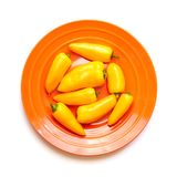 Pimientas amarillas en la placa anaranjada aislada en blanco imagen de archivo libre de regalías