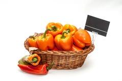 Pimientas anaranjadas en una cesta de la tienda Fotos de archivo
