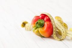 Pimientas crudas coloridas dulces con centímetro en blanco fotografía de archivo