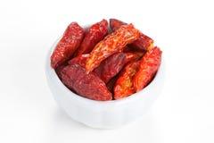 Pimientas de chile caliente en un tazón de fuente en el fondo blanco Fotos de archivo