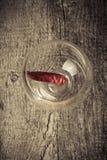 Pimientas de chile candentes en un vidrio en un fondo de madera oscuro Foto de archivo