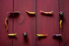 Pimientas de Chile en fondo de madera rojo Visi?n superior imagen de archivo