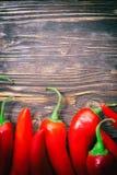Pimientas de chile en una tabla Imágenes de archivo libres de regalías