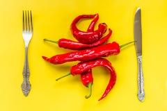 Pimientas de chile picantes rojas en amarillo Fotos de archivo