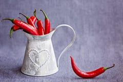 Pimientas de chile rojo calientes en una cesta gris del metal en backgroun azulado Foto de archivo libre de regalías