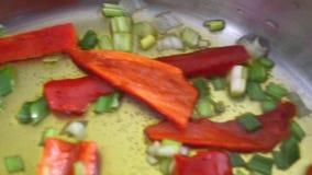 Pimientas de chile rojo y el freír fresco de las cebollas almacen de metraje de vídeo