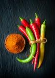 Pimientas de chile rojo y pimientas de chile verdes en una pizarra de la pizarra Foto de archivo