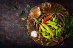 Pimientas de chile verdes en una cesta en un fondo oscuro Foto de archivo