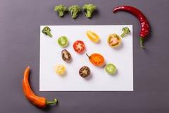 Pimientas de chiles con los tomates y el bróculi en fondo gris y blanco fotos de archivo