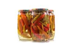 Pimientas de chiles conservadas en vinagre preservadas en los tarros de cristal en Backgrou blanco Fotografía de archivo libre de regalías