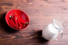 Pimientas de chiles en una placa y un jarro rojos de leche en una tabla marrón t Fotos de archivo libres de regalías