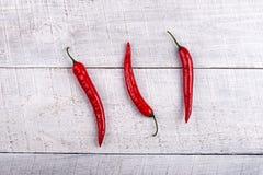 Pimientas de chiles rojos maduras en la tabla imagen de archivo