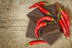 Pimientas del chocolate oscuro y de chile rojo Venta del chocolate picante Gusto loco foto de archivo libre de regalías