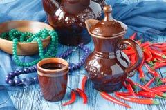 Pimientas del jarro y de chile de la arcilla en un fondo de madera Foto de archivo