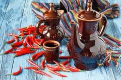 Pimientas del jarro y de chile de la arcilla en un fondo de madera Foto de archivo libre de regalías