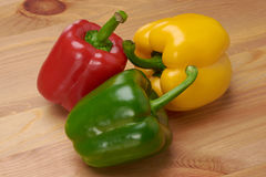 Pimientas dulces verdes y amarillas rojas en la tabla Imagen de archivo libre de regalías