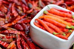 Pimientas frescas en el cuenco blanco y pimientas rojas secadas de calidad inferior Foto de archivo libre de regalías