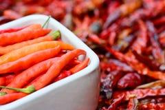 Pimientas frescas en el cuenco blanco y pimientas rojas secadas de calidad inferior Fotografía de archivo libre de regalías