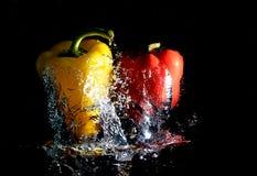 Pimientas que caen en el agua Foto de archivo