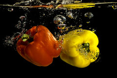 Pimientas que caen en el agua Imagen de archivo