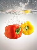Pimientas que salpican en agua Imagen de archivo libre de regalías