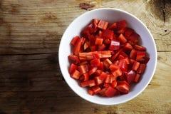 Pimientas rojas cortadas en un cuenco blanco en un fondo de madera rústico Imagen de archivo