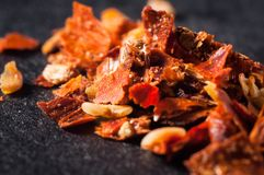 Pimientas rojas machacadas con las semillas en un primer oscuro del fondo foto de archivo libre de regalías