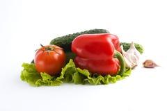 Pimientas rojas y pimientas amarillas con los tomates en un abackgro blanco Foto de archivo libre de regalías