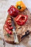 Pimientas rojas y amarillas en tablero de madera verde oliva Foto de archivo libre de regalías