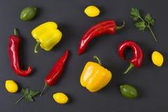 Pimientas rojas y amarillas en un fondo negro alimento dietético Vehículos en un fondo negro Pimientas en la tabla Fotos de archivo libres de regalías