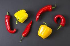 Pimientas rojas y amarillas en un fondo negro alimento dietético Vehículos en un fondo negro Pimientas en la tabla Imagen de archivo libre de regalías