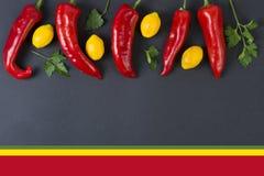 Pimientas rojas y amarillas en un fondo negro alimento dietético Vehículos en un fondo negro Pimientas en la tabla Imágenes de archivo libres de regalías