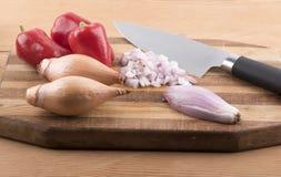Pimientas rojas y cebollas en una tajadera de madera con un cuchillo Imagenes de archivo