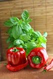 Pimientas rojas y hojas de la albahaca Foto de archivo libre de regalías
