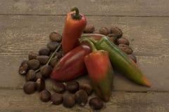 Pimientas rojas y verdes en la tabla de madera áspera Fotografía de archivo