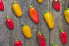 Pimientas vegetales amarillas y rojas en el fondo de madera Foto de archivo