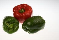 Pimientas verdes y rojas con descensos del agua en blanco foto de archivo libre de regalías