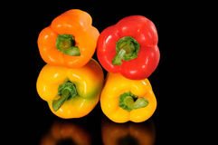 Pimiento above pimiento. Group of four pimientos,orange,red and yellow on dark background Royalty Free Stock Image