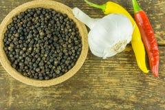 Pimientos picantes de diversos colores, de la pimienta negra y del ajo Foto de archivo