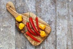 Pimientos picantes rojos y amarillos en tabla de cortar Fotografía de archivo libre de regalías