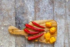 Pimientos picantes rojos y amarillos en tabla de cortar Imagen de archivo libre de regalías