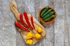 Pimientos picantes rojos y amarillos en tabla de cortar con pimientas verdes en un cuenco Foto de archivo