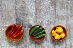 Pimientos picantes verdes y amarillos rojos en cuencos Fotografía de archivo libre de regalías