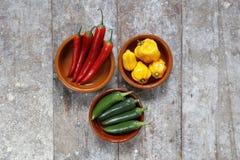 Pimientos picantes verdes y amarillos rojos en cuencos Imagen de archivo libre de regalías