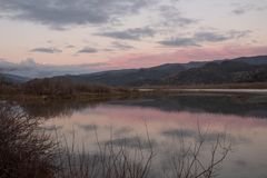 Pink sky reflecting in Oregon`s Rogue River at sunset. Winter reflections of pink and grey clouds at sunset in Oregon`s Rogue River near Gold Beach royalty free stock photo