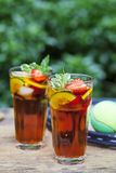 Pimms in the garden with tennis racket. Pimms and lemonade in the garden with tennis racket and tennis ball Royalty Free Stock Photo