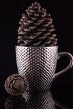 Pimpled silverkaffekopp med en stor pinecone inom på den reflekterande svarta yttersidan Och den andra lilla pineconen Arkivbilder